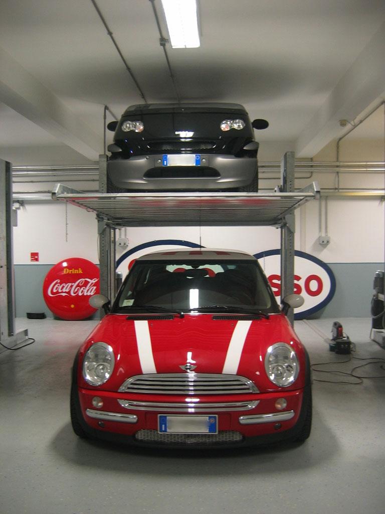 Sistema per parcheggio auto senza fossa a comando elettrico con movimentazioni oleodinamiche a due posti sovrapposti inseribile in qualsiasi ambiente senza alcun bisogno di opere murarie.